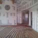 Maison Organique bois et thermopierre en Vendée vue du volume séjour lors de la pose du plancher chauffant